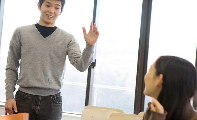 学内で軽く挨拶する女学生と男性
