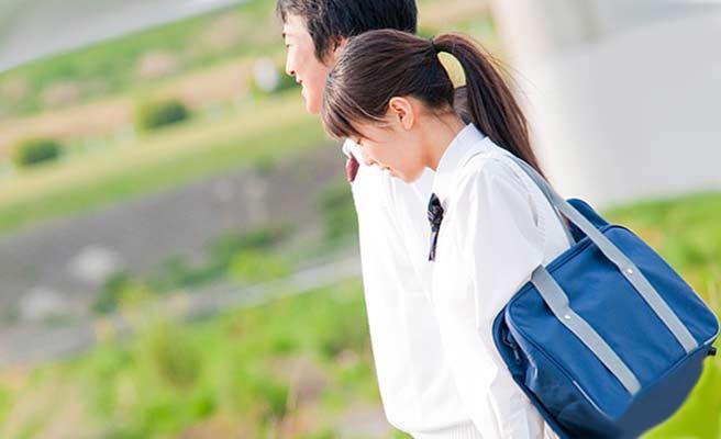 一緒に通学路を歩く学生カップル