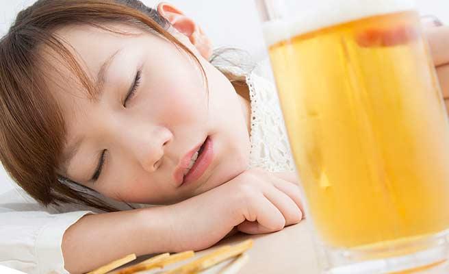 ビールを片手に机に顔をつけて目を閉じる女性