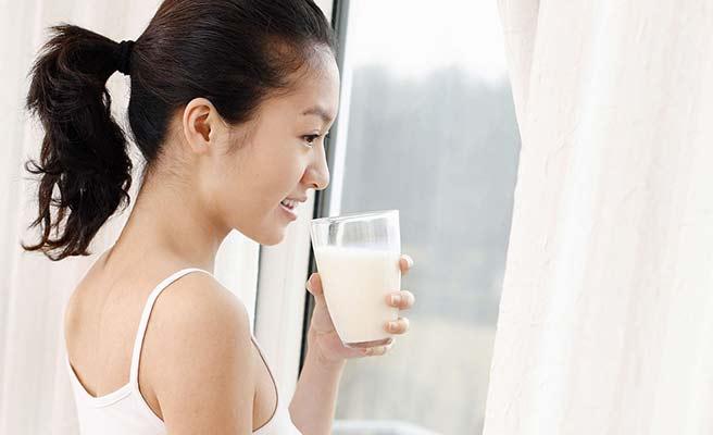 窓から外を見ながらミルクを飲む女性