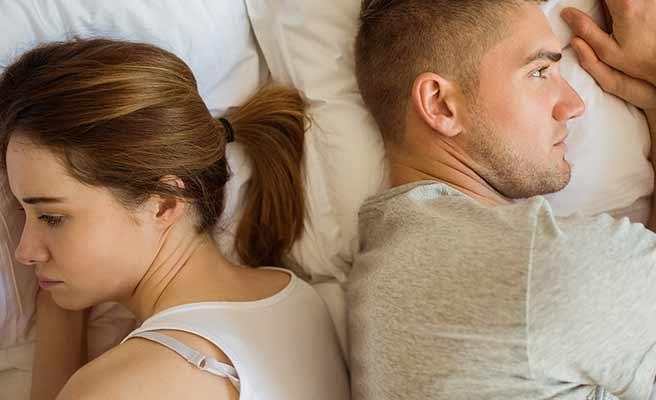 ベッドの上で背中合わせのカップル