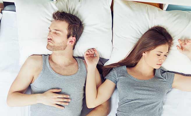 寝台の中で腕をつけて眠るカップル