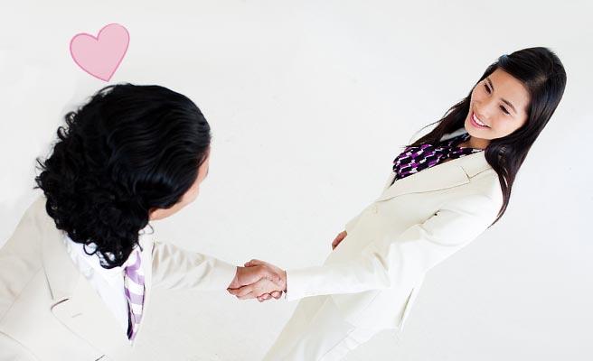 女性と握手する男性の上にハートマーク