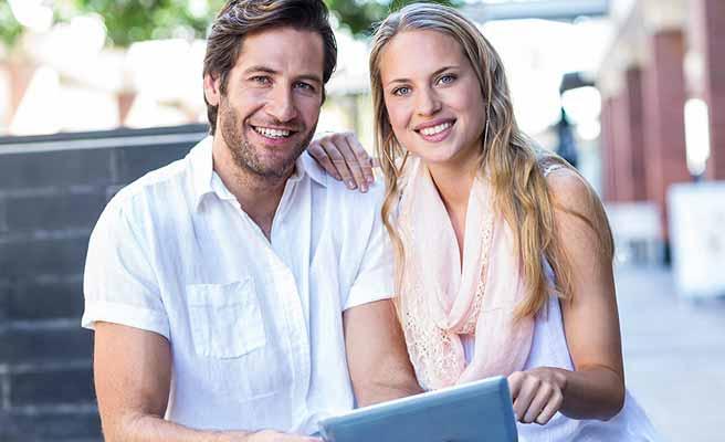 ハンサムな男性と一緒にタブレットを見る女性