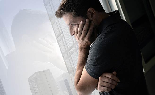 窓辺に立って一人外を見る男性