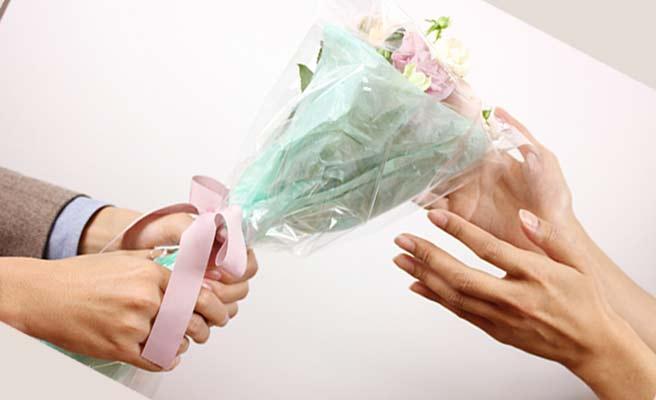 男性が女性に花束を渡す