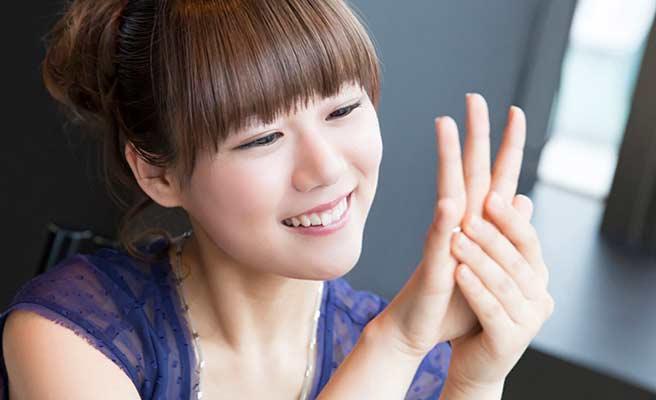 指にはめた指輪を眺める女性