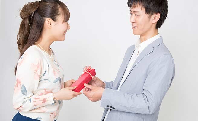 女性にプレゼントを手渡す男性
