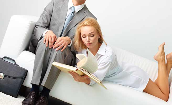 スーツ姿の男性の隣で本を読む女性