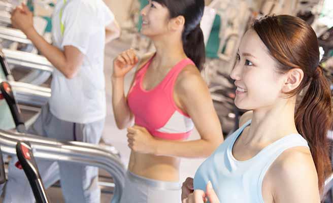 ジムでランナーマシンで運動する女性