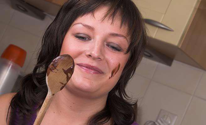 ほっぺたにチョコレートつけて台所でつまみ食いする女性