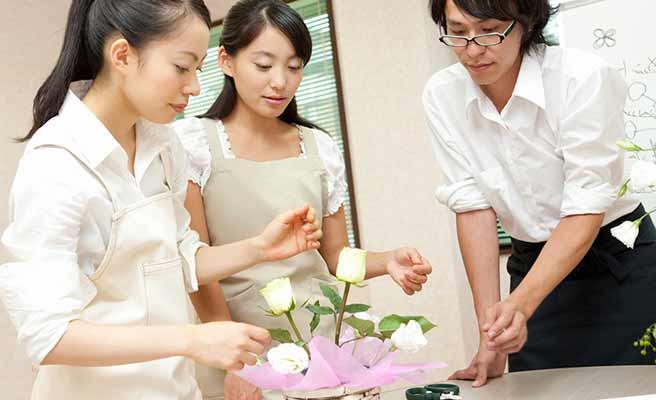 男女が文化教室で花を活けている