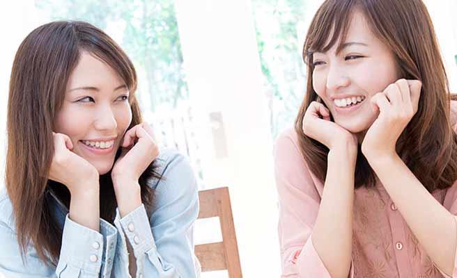 互いに笑顔で会話する女性二人