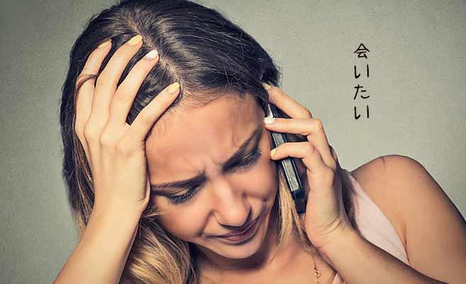 泣き出しそうな表情でスマホを耳に当てる女性
