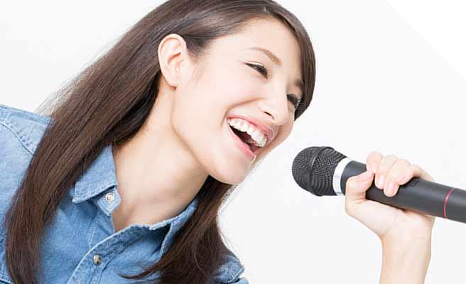 マイクをもって歌う女性