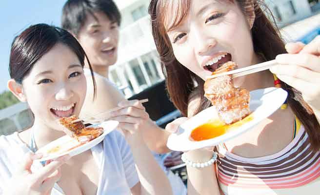 BBQで肉を食べる女性たち