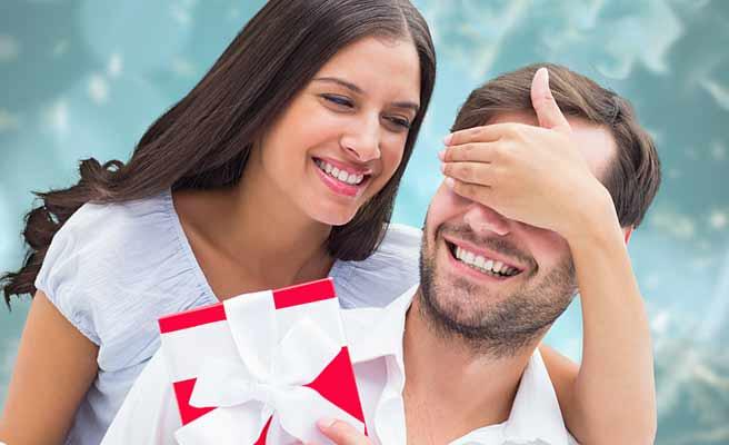 彼氏の目を手で覆いながらプレゼントを渡す女性