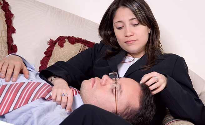 彼氏を膝枕で寝せて見つめる女性