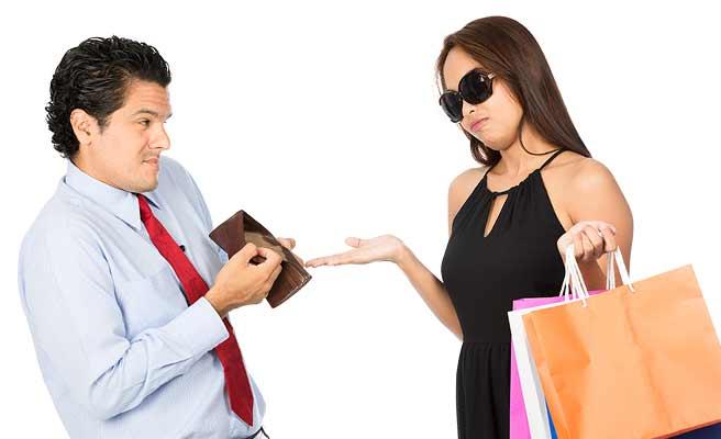 買い物する女性に空の財布を見せる男性