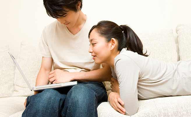 一緒にノートパソコンを見る夫婦