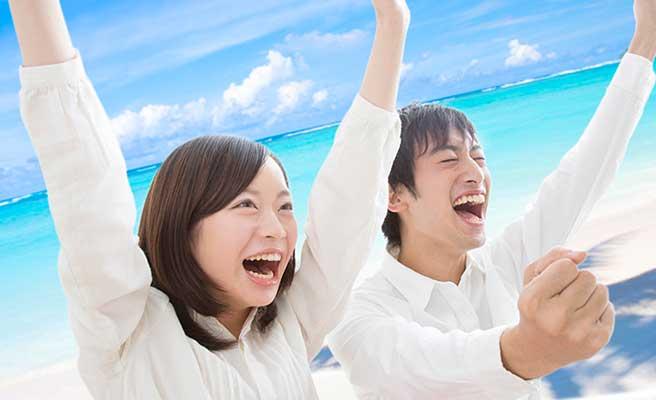 海を背景に歓喜するカップル