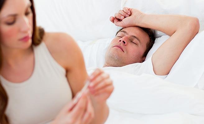 ベッドに寝る夫の熱を計る妻
