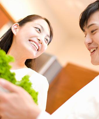 夫婦で野菜を持った皿を運んでいる
