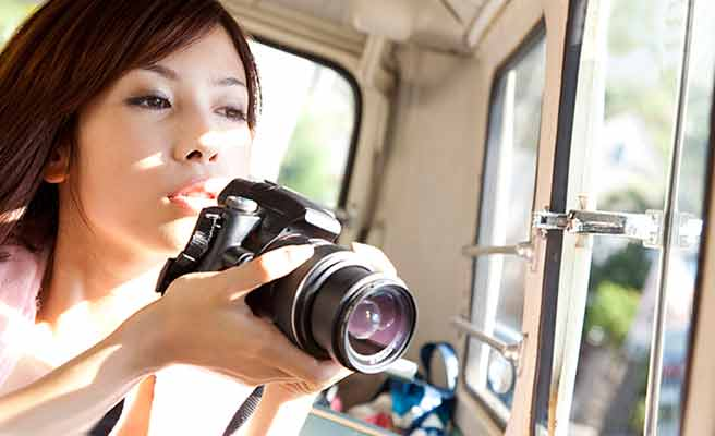 バスの中からカメラで風景を撮影する女性