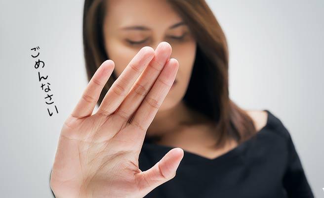 片手で拒否る女性