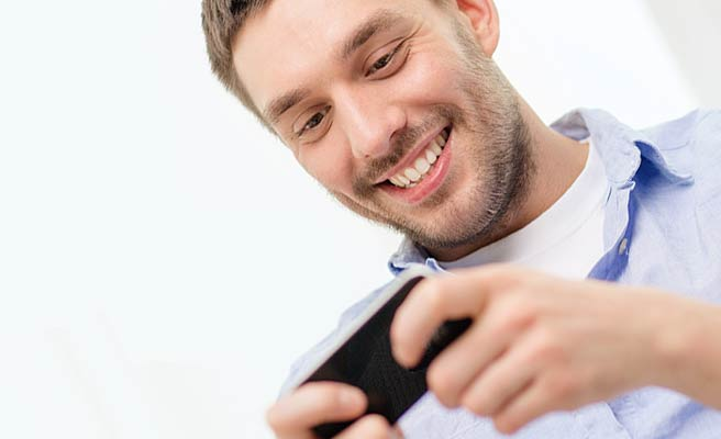 スマホを見て笑顔になる男性
