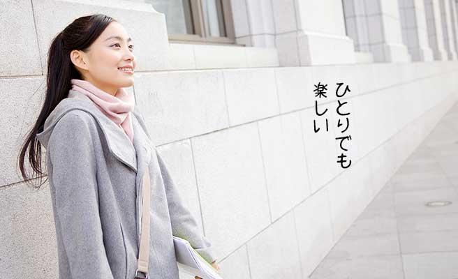 長い壁の端に立って前を見つめる女性