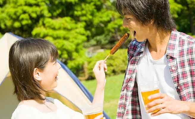 キャンプ場で一緒に食事する男女
