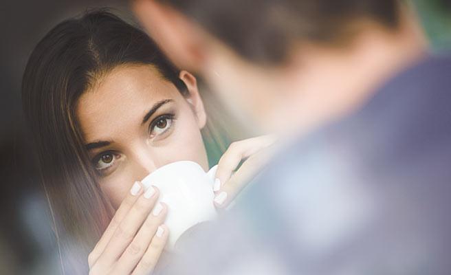 男性とお茶しながら相手を見つめる女性