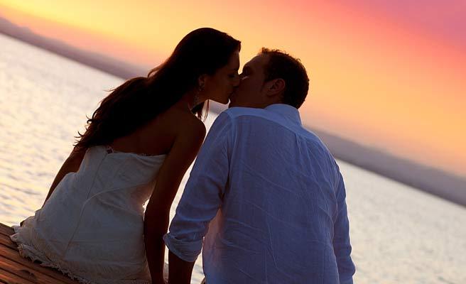 夕暮れの海辺でキスするカップル