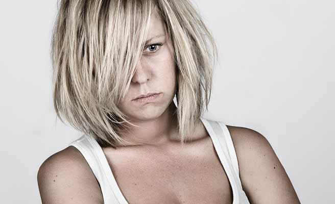 手入れしてない髪を垂らして思いつめる女性