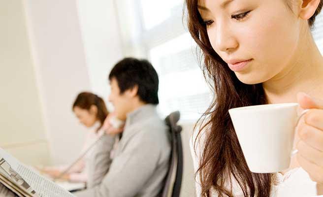 職場で一人コーヒーを飲む女性