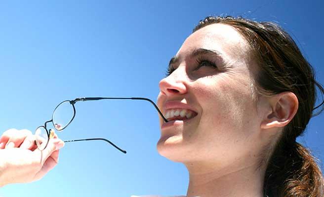 眼鏡のつるを噛みながら空を見上げる女性