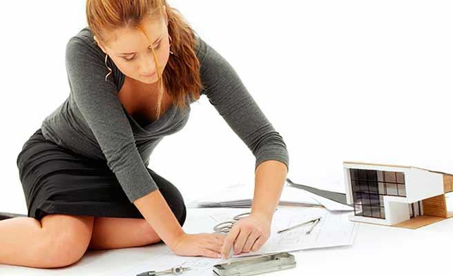 建築模型と設計図を見る女性