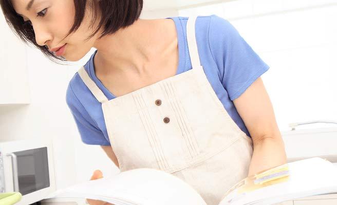 料理本を見ながら調理する女性