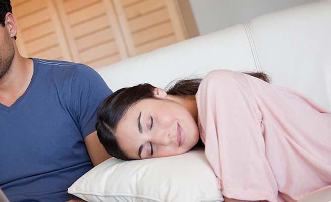 彼氏の傍でソファのクッションに頭をのせる女性