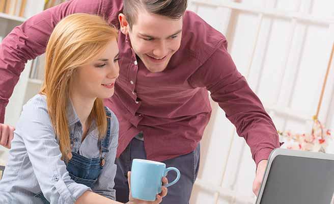 一緒にパソコンを見ながら会話するカップル