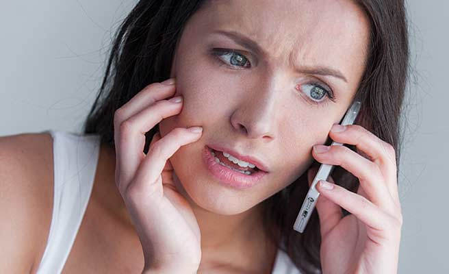 スマホで連絡を受けて哀しい表情の女性