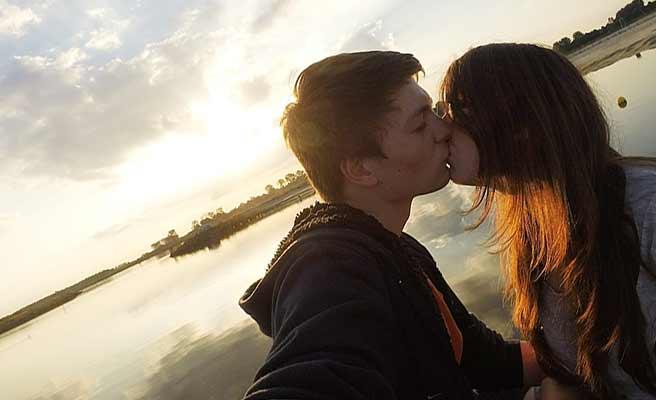 夕暮れの湖畔でキスするカップル