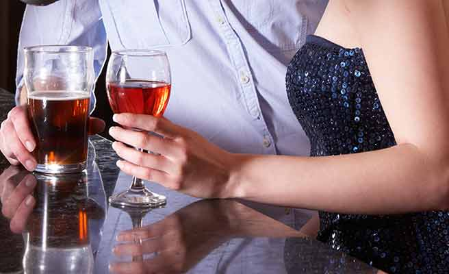 バーのカウンターでグラスを持つ男女
