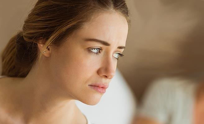寝台の上で不安げな表情で見つめる女性