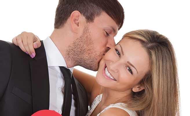女性の頬に唇をつけて言い寄る男性