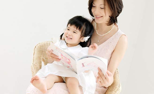 子供を抱いて絵本を読んであげる母親