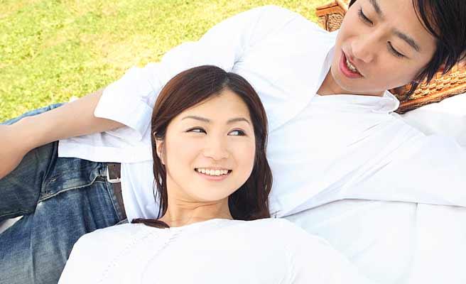 恋人と芝生に寝そべる女性