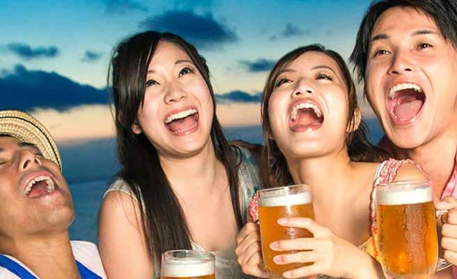 戸外の飲み会でビールで乾杯する男女