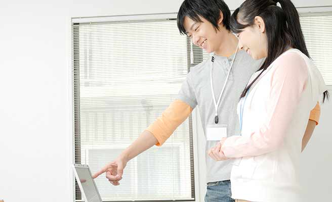パソコンを指さす同僚男性の傍に立つ女性